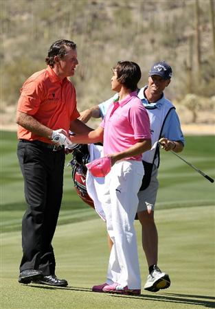 MARANA, AZ - FEBRUARY 24:  Phil Mickelson (R) congrulates Rickie Fowler (C) on his win on the 13th hole as caddie Jim 'Bones' Mackay (R) looks on during the second round of the Accenture Match Play Championship at the Ritz-Carlton Golf Club on February 24, 2011 in Marana, Arizona.  (Photo by Andy Lyons/Getty Images)
