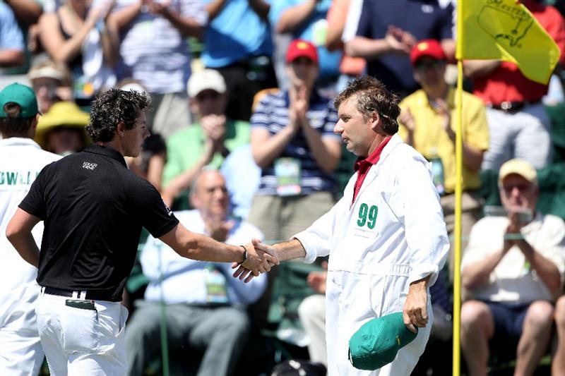 AUGUSTA, GA - APRIL 07:  Rory McIlroy of Northern Ireland shakes hands with his caddie JP Fitzgerald on the 18th green after finishing with a seven-under par 65 during the first round of the 2011 Masters Tournament at Augusta National Golf Club on April 7, 2011 in Augusta, Georgia.  (Photo by Andrew Redington/Getty Images)