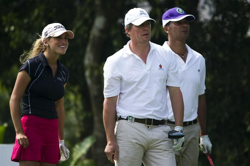 HAIKOU, CHINA - OCTOBER 30:  Spanish golfer Belen Mozo (L), Hugh Grant (C) of Great Britain and Ruud Gullit of the Netherlands look on at the 10th tee during day four of the Mission Hills Start Trophy tournament at Mission Hills Resort on October 30, 2010 in Haikou, China. The Mission Hills Star Trophy is Asia's leading leisure liflestyle event and features Hollywood celebrities and international golf stars.  (Photo by Victor Fraile/Getty Images for Mission Hills)