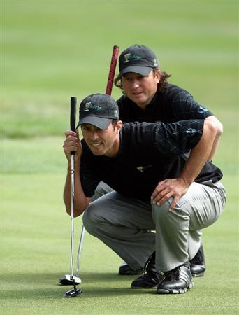 SAN FRANCISCO - OCTOBER 08:  Tim Clark of South Africa and the International Team helps his partner Mike Weir of Canada line up a putt at the 3rd hole during the Day One Foursome Matches in The Presidents Cup at Harding Park Golf Course on October 8, 2009 in San Francisco, California  (Photo by David Cannon/Getty Images)