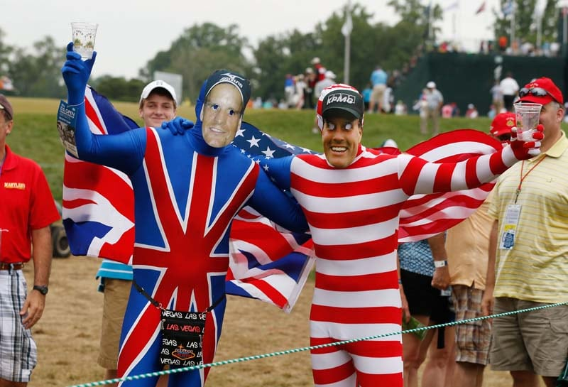 Two fans wear Union Jack costumes and cut-out faces of Luke Donald of England and Phil Mickelson