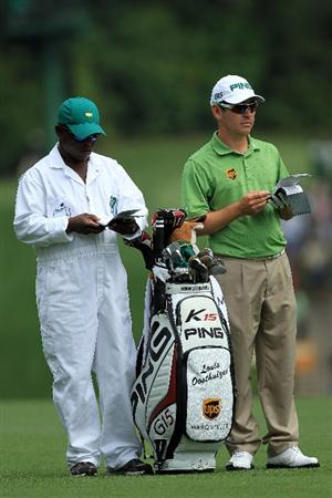 AUGUSTA, GA - APRIL 08:  Louis Oosthuizen of South Africa looks on alongside his caddie Zacharia Rasego before hitting his second shot on the fifth hole during the second round of the 2011 Masters Tournament at Augusta National Golf Club on April 8, 2011 in Augusta, Georgia.  (Photo by David Cannon/Getty Images)