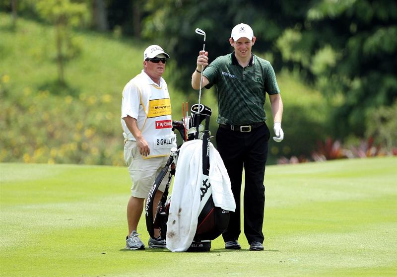 KUALA LUMPUR, MALAYSIA - MARCH 05:  Stephen Gallacher of Scotland waits with his caddie on the 17th hole during the the second round of the Maybank Malaysian Open at the Kuala Lumpur Golf and Country Club on March 5, 2010 in Kuala Lumpur, Malaysia.  (Photo by Andrew Redington/Getty Images)