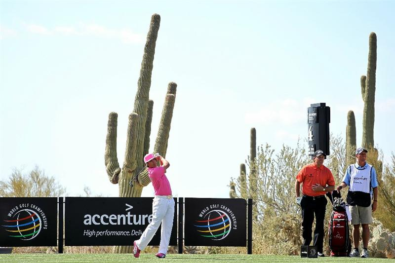 MARANA, AZ - FEBRUARY 24:  Rickie Fowler hits his tee shot on the fourth hole as Phil Mickelson and caddie Jim 'Bones' Mackay look on during the second round of the Accenture Match Play Championship at the Ritz-Carlton Golf Club on February 24, 2011 in Marana, Arizona.  (Photo by Andy Lyons/Getty Images)