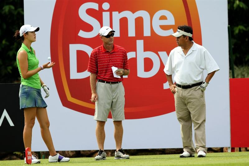 KUALA LUMPUR, MALAYSIA - OCTOBER 21:   Michelle Wie of USA speaks to her caddie on the 10th hole during the Sime Darby Pro-Am at the KLGCC Golf Course on October 21, 2010 in Kuala Lumpur, Malaysia (Photo by Stanley Chou/Getty Images)