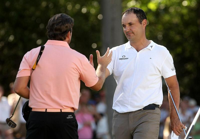 VIRGINIA WATER, ENGLAND - MAY 23:  Simon Khan of England is congratulated by Graeme McDowell (L) of Northern Ireland on the 18th green during the final round of the BMW PGA Championship on the West Course at Wentworth on May 23, 2010 in Virginia Water, England.  (Photo by Andrew Redington/Getty Images)