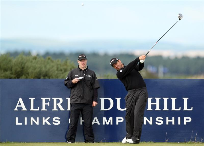 ST ANDREWS, UNITED KINGDOM - SEPTEMBER 30:  Padraig Harrington of Ireland drives off the 16th tee watched by his caddie Ronan Flood during the practice round of The Alfred Dunhill Links Championship at The Old Course on September 30, 2008 in St Andrews, Scotland.  (Photo by Ross Kinnaird/Getty Images)
