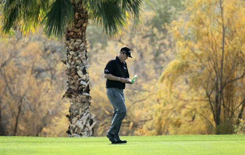 LA QUINTA, CA - JANUARY 19:  J.J. Henry checks his book as he walks on the fairway on the 16th hole during round one of the Bob Hope Classic at the Nicklaus Private Course at PGA West on January 19, 2011 in La Quinta, California.  (Photo by Stephen Dunn/Getty Images)