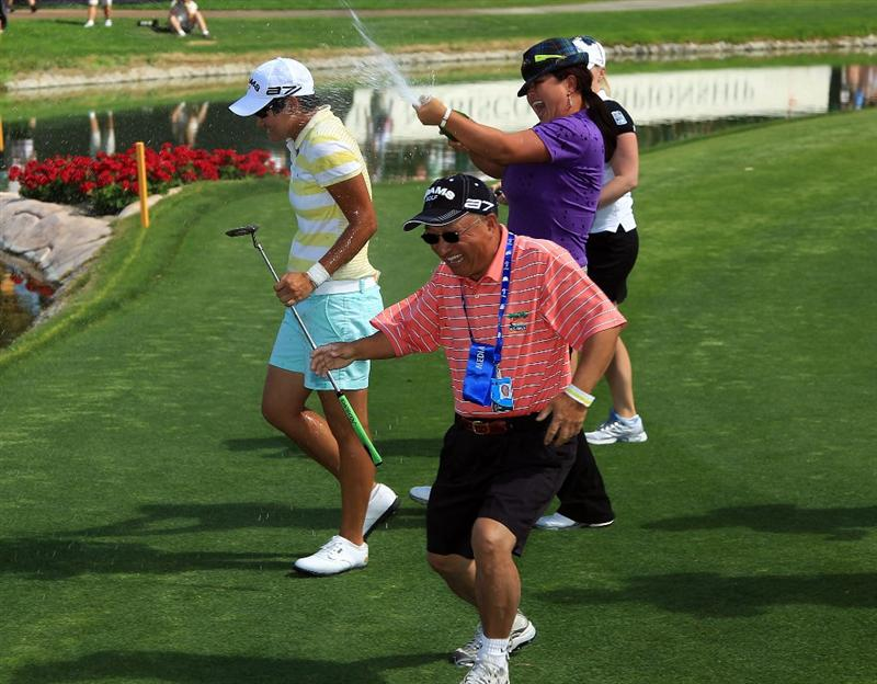 RANCHO MIRAGE, CA - APRIL 04:  Yani Tseng of Taiwan is chased by fellow LPGA player Christina Kim after as Yani Tseng's father takes evasive action after Tseng had holed the winning putt on the 18th green during the final round of the 2010 Kraft Nabisco Championship, on the Dinah Shore Course at The Mission Hills Country Club, on April 4, 2010 in Rancho Mirage, California.  (Photo by David Cannon/Getty Images)