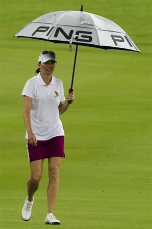 CHON BURI, THAILAND - FEBRUARY 20:  Stacy Prammanasudh of USA shelters from the rain under her umbrella on the 5th green during round three of the Honda PTT LPGA Thailand at Siam Country Club on February 20, 2010 in Chon Buri, Thailand.  (Photo by Victor Fraile/Getty Images)