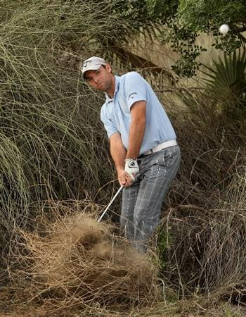 DUBAI, UNITED ARAB EMIRATES - FEBRUARY 05:  Oliver Wilson of England plays his second shot from an awkward lie on the 17th hole during the second round of the Omega Dubai Desert Classic on February 5, 2010 in Dubai, United Arab Emirates.  (Photo by Andrew Redington/Getty Images)