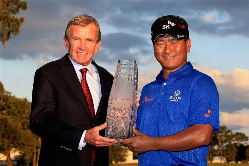 PONTE VEDRA BEACH, FL - MAY 15:  K.J. Choi of South Korea (R) celebrates with the trophy alongside PGA TOUR Commissioner Tim Finchem (L) after defeating David Toms on the first playoff hole to win THE PLAYERS Championship held at THE PLAYERS Stadium course at TPC Sawgrass on May 15, 2011 in Ponte Vedra Beach, Florida.  (Photo by Sam Greenwood/Getty Images)