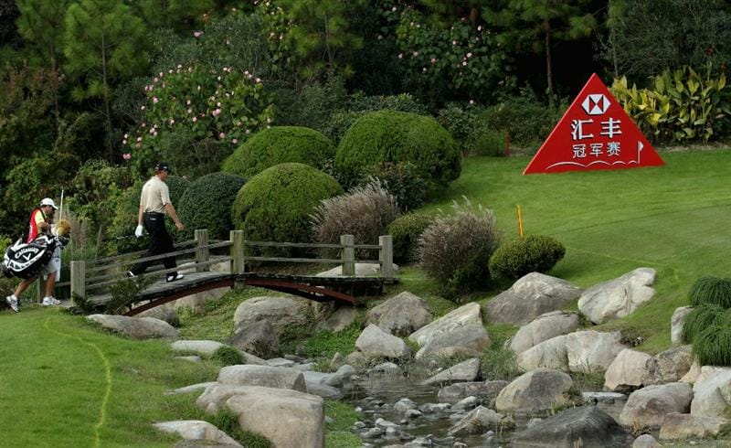 SHANGHAI, CHINA - NOVEMBER 06:  Ernie Els of South Africa and his caddie Michael Kerr cross a bridge on the eighth hole uring the third round of the WGC-HSBC Champions at Sheshan International Golf Club on November 6, 2010 in Shanghai, China.  (Photo by Andrew Redington/Getty Images)