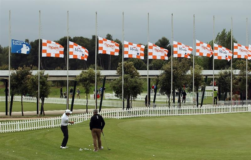 BARCELONA, SPAIN - MAY 07:  A golfer practices on the putting green as flgs fly half mast during the third round of the Open de Espana at the the Real Club de Golf El Prat on May 7 , 2011 in Barcelona, Spain.  (Photo by Ross Kinnaird/Getty Images)