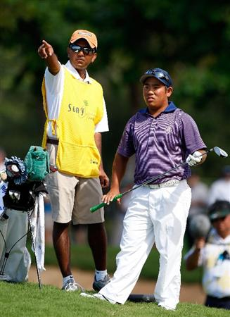 HONOLULU - JANUARY 17:  Tadd Fujikawa and caddie Shakil Ahmed look over a shot on the 18th hole during the third round of the Sony Open at Waialae Country Club on January 17, 2009 in Honolulu, Hawaii.  (Photo by Sam Greenwood/Getty Images)