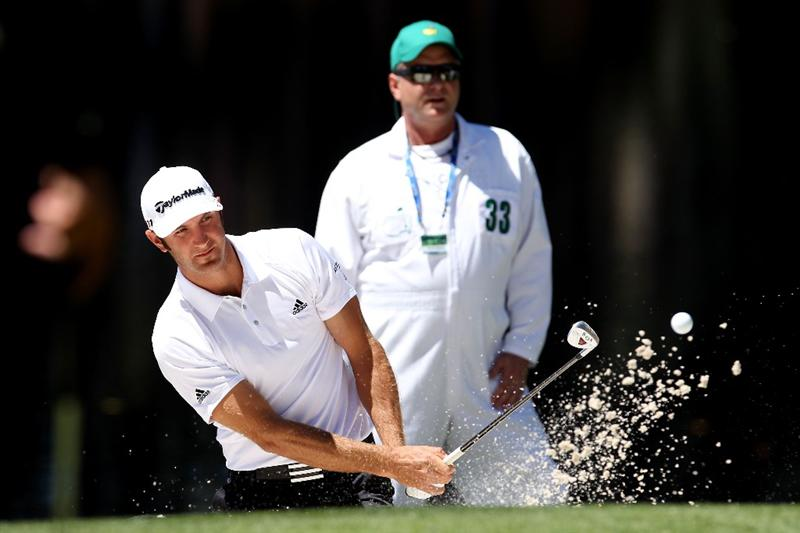 AUGUSTA, GA - APRIL 06:  Dustin Johnson plays a bunker shot as his caddie looks on during the Par 3 Contest prior to the 2011 Masters Tournament at Augusta National Golf Club on April 6, 2011 in Augusta, Georgia.  (Photo by Andrew Redington/Getty Images)