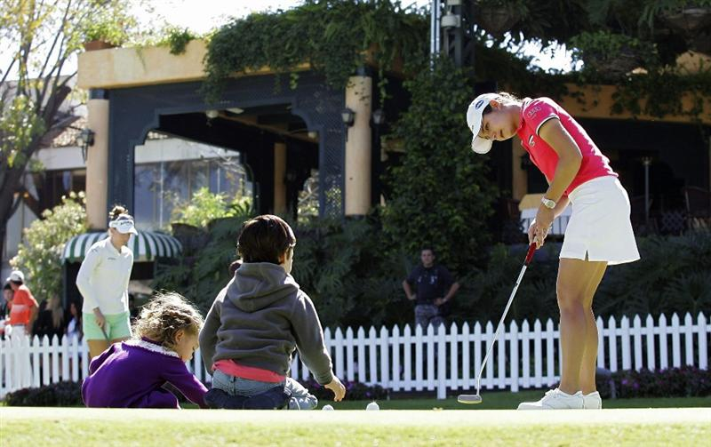 GUADALAJARA, MEXICO - NOVEMBER 13:  Lorena Ochoa (R) of Mexico putts balls to her niece and nephew on the putting green during the third round of the Lorena Ochoa Invitational Presented by Banamex and Corona Light at Guadalajara Country Club on November 13, 2010 in Guadalajara, Mexico.  (Photo by Michael Cohen/Getty Images)