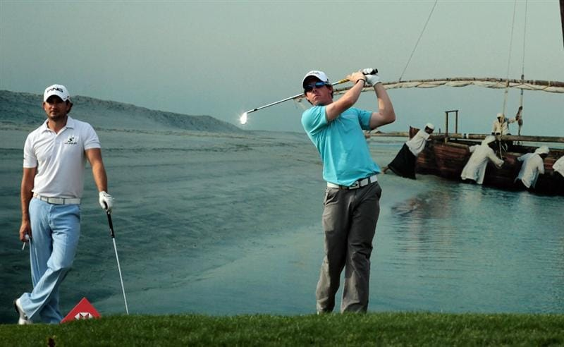ABU DHABI, UNITED ARAB EMIRATES - JANUARY 22:  Rory McIlroy of Northern Ireland playing his tee shot at the 15th hole watched by his playing partner Gareth Maybin of Northern Ireland during the third round of the 2011 Abu Dhabi HSBC Golf Championship held at the Abu Dhabi Golf Club on January 22, 2011 in Abu Dhabi, United Arab Emirates.  (Photo by David Cannon/Getty Images)