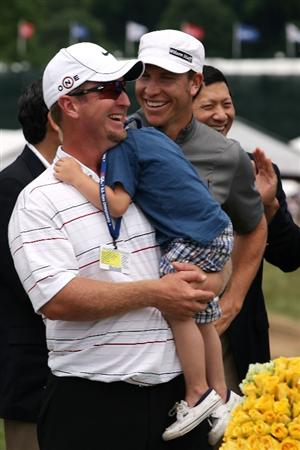 FARMINGDALE, NY - JUNE 22:  David Duval smiles while holding his two year old son Brayden during the trophy presentation while Ricky Barnes looks on after the final round of the 109th U.S. Open on the Black Course at Bethpage State Park on June 22, 2009 in Farmingdale, New York.  (Photo by Andy Lyons/Getty Images)