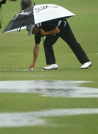 MELBOURNE, AUSTRALIA - NOVEMBER 13: Andre Stolz of Australia picks his ball out of a puddle during round three of the Australian Masters at The Victoria Golf Club on November 13, 2010 in Melbourne, Australia.  (Photo by Ryan Pierse/Getty Images)