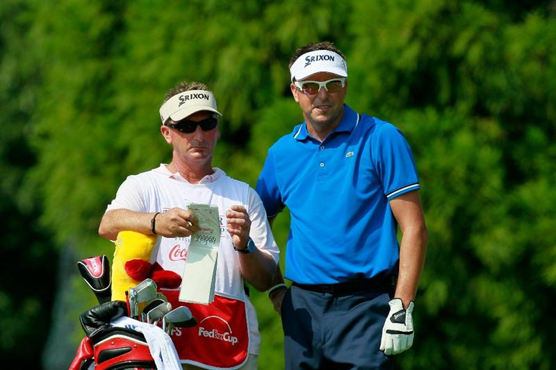 ATLANTA - SEPTEMBER 23:  Robert Allenby of Australia (R) talks with his caddie Colin Burwood (L) on the second hole tee during the first round of THE TOUR Championship presented by Coca-Cola at East Lake Golf Club on September 23, 2010 in Atlanta, Georgia.  (Photo by Kevin C. Cox/Getty Images)
