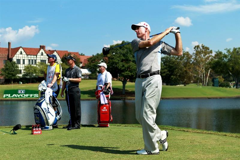 ATLANTA - SEPTEMBER 25:  Jim Furyk (R) hits his tee shot on the seventh hole while Luke Donald of England (2nd L), caddie John McLaren (L) and caddie Mike 'Fluff' Cowan (2nd R) look on during the third round of THE TOUR Championship presented by Coca-Cola at East Lake Golf Club on September 25, 2010 in Atlanta, Georgia.  (Photo by Scott Halleran/Getty Images)