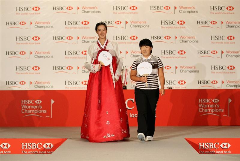 SINGAPORE - FEBRUARY 22:  Michelle Wie of the USA wears traditional Korean dress alongside Jiyai Shin of South Korea during a photocall at the Fairmont Hotel prior to the start of the HSBC Women's Champions at the Tanah Merah Country Club on February 22, 2011 in Singapore.  (Photo by Andrew Redington/Getty Images)