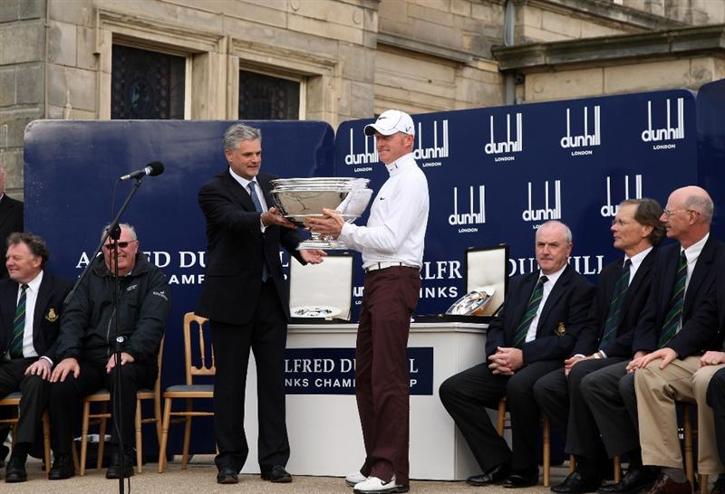 ST ANDREWS, SCOTLAND - OCTOBER 05:  Simon Dyson of England is presented with the trophy by Christopher Colfer, Chief executive of Alfred Dunhill after victory at the The Alfred Dunhill Links Championship at The Old Course on October 5, 2009 in St.Andrews, Scotland.  (Photo by David Cannon/Getty Images)