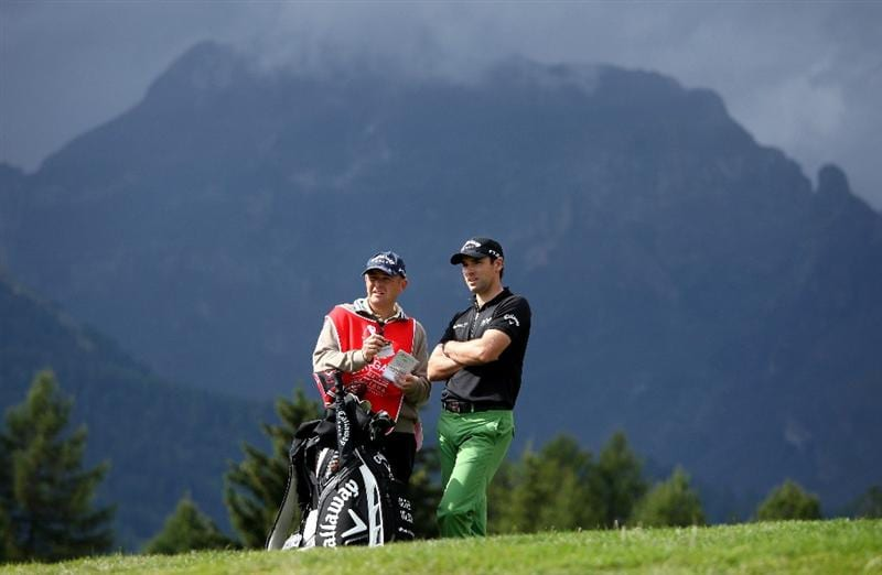 CRANS, SWITZERLAND - SEPTEMBER 03:  Oliver Wilson of England waits with his caddie Richard Hill on the 12th hole during the first round of The Omega European Masters at Crans-Sur-Sierre Golf Club on September 3, 2009 in Crans Montana, Switzerland.  (Photo by Andrew Redington/Getty Images)