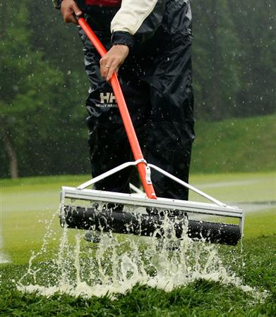 FARMINGDALE, NY - JUNE 18:  A memeber of the grounds crew works on a soggy 18th green during the first round of the 109th U.S. Open on the Black Course at Bethpage State Park on June 18, 2009 in Farmingdale, New York.  (Photo by Andrew Redington/Getty Images)
