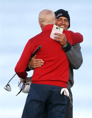 KINGSBARNS, SCOTLAND - OCTOBER 04:  Simon Dyson of England is congratulated by his playing partner US surfer Kelly Slater on the 18th green after his finishes his round during the third round of The Alfred Dunhill Links Championship at Kingsbarns Golf Links on October 4, 2009 in Kingsbarns, Scotland.The third round was postponed on Saturday due to gale force winds.  (Photo by Andrew Redington/Getty Images)