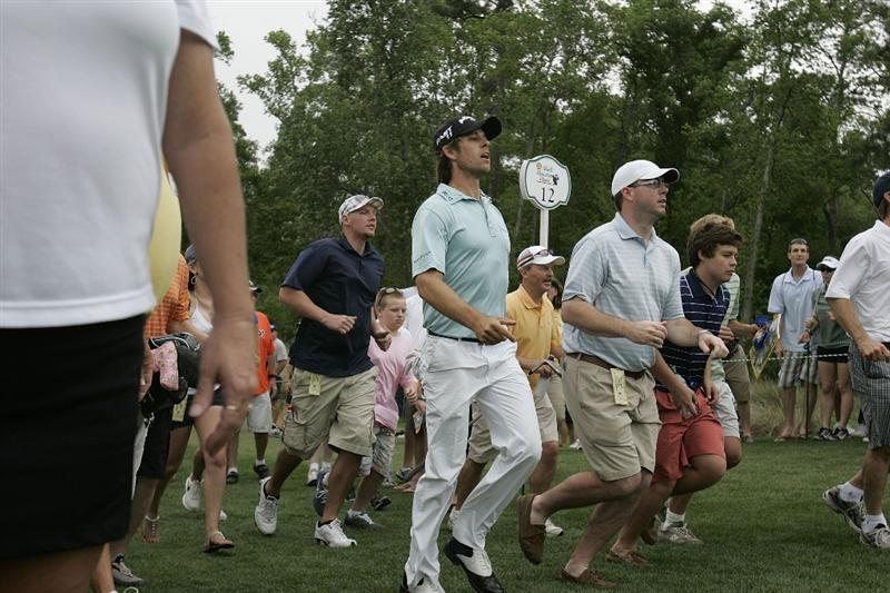 HUMBLE, TX - APRIL 03: Aaron Baddeley of Australia is joined by members of the gallery as he rushes to glimpse his second shot on the 12th hole during the final round of the Shell Houston Open at Redstone Golf Club on April 3, 2011 in Humble, Texas.  (Photo by Michael Cohen/Getty Images)