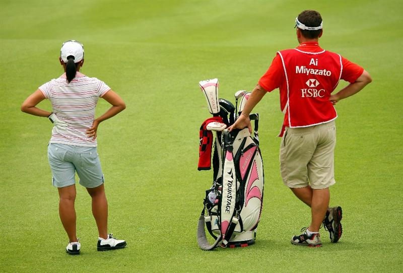 SINGAPORE - MARCH 07:  Ai Miyazato of Japan waits with her caddie on the ninth hole during the third round of the HSBC Women's Champions at Tanah Merah Country Club on March 7, 2009 in Singapore.  (Photo by Andrew Redington/Getty Images)