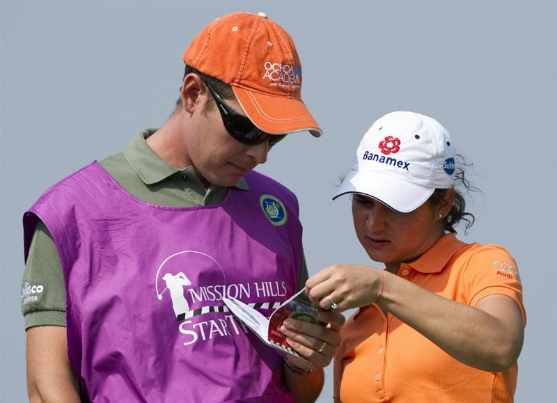 HAIKOU, CHINA - OCTOBER 30:  Lorena Ochoa (R) of Mexico looks to her yardage book near her caddie on the 4th green during day four of the Mission Hills Start Trophy tournament at Mission Hills Resort on October 30, 2010 in Haikou, China. The Mission Hills Star Trophy is Asia's leading leisure liflestyle event and features Hollywood celebrities and international golf stars.  (Photo by Victor Fraile/Getty Images for Mission Hills)