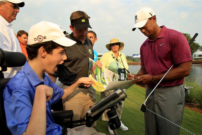 PONTE VEDRA BEACH, FL - MAY 11:  Tiger Woods (R) signs his autograph for a fan during a practice round prior to the start of THE PLAYERS Championship held at THE PLAYERS Stadium course at TPC Sawgrass on May 11, 2011 in Ponte Vedra Beach, Florida.  (Photo by Streeter Lecka/Getty Images)