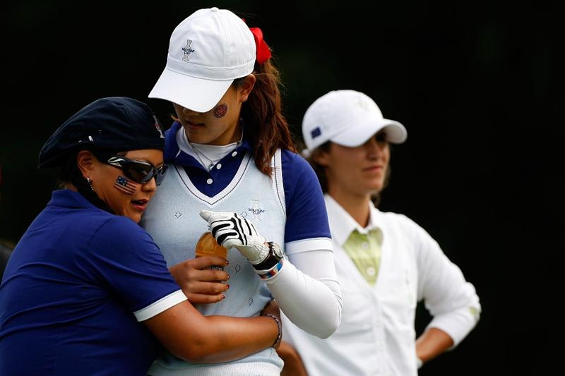 SUGAR GROVE, IL - AUGUST 22:  Christina Kim left, hugs Michelle Wie of the U.S. Team next to Tania Elosegui of the European Team on the 7th hole during the Saturday morning Fourball matches at the 2009 Solheim Cup at Rich Harvest Farms on August 22, 2009 in Sugar Grove, Illinois.  (Photo by Chris Graythen/Getty Images)