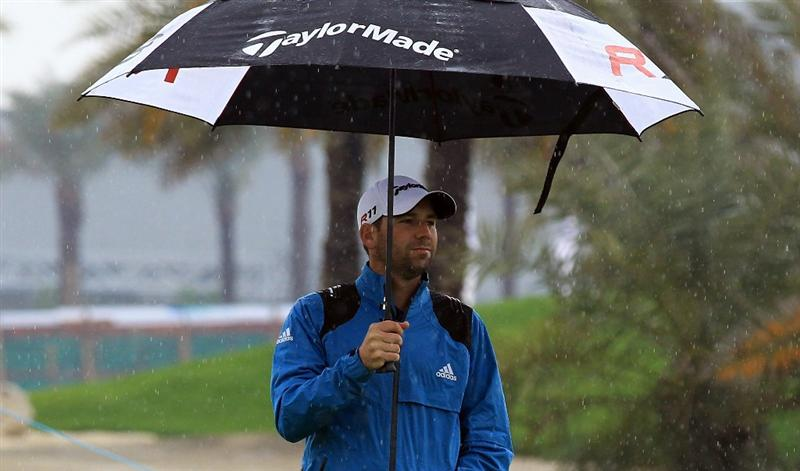 BAHRAIN, BAHRAIN - JANUARY 26:  Sergio Garcia of Spain shelters under his umbrella in the rain during the pro-am for the 2011 Volvo Champions held at the Royal Golf Club on January 26, 2011 in Bahrain, Bahrain.  (Photo by David Cannon/Getty Images)