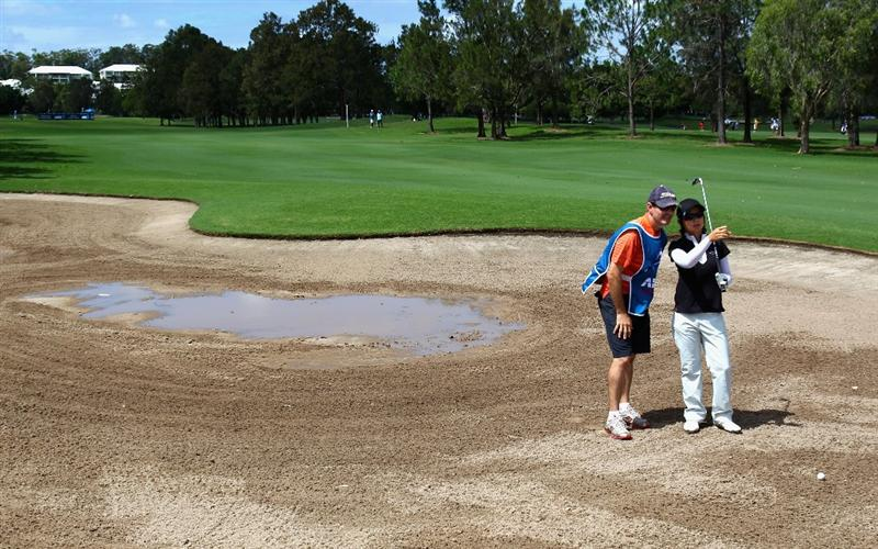 GOLD COAST, AUSTRALIA - MARCH 04:  Eun Hee Ji of Korea prepares to play a shot out of the flooded bunker on the 9th hole during round one of the 2010 ANZ Ladies Masters at Royal Pines Resort on March 4, 2010 in Gold Coast, Australia.  (Photo by Ryan Pierse/Getty Images)