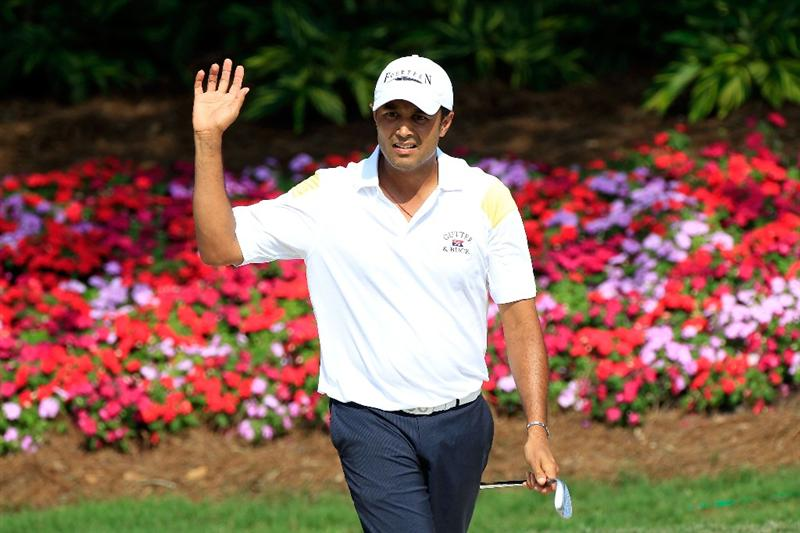 PONTE VEDRA BEACH, FL - MAY 12:  Arjun Atwal of India waves after holing out from a bunker on the 14th hole for birdie during the first round of THE PLAYERS Championship held at THE PLAYERS Stadium course at TPC Sawgrass on May 12, 2011 in Ponte Vedra Beach, Florida.  (Photo by Sam Greenwood/Getty Images)