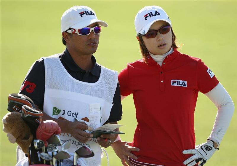PHOENIX - MARCH 27:  Eun-Hee Ji of South Korea talks with caddie Zack Austin on the 18th hole fairway during the second round of the J Golf Phoenix LPGA International golf tournament at Papago Golf Course on March 27, 2009 in Phoenix, Arizona.  (Photo by Christian Petersen/Getty Images)
