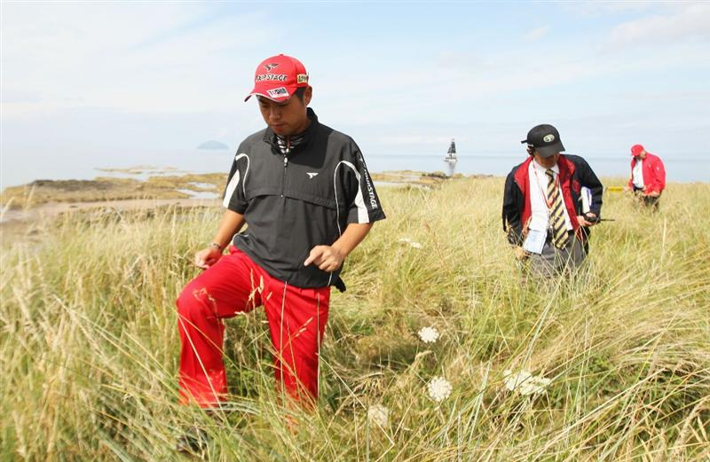 TURNBERRY, SCOTLAND - JULY 16:  Yuta Ikeda of Japan looks for his ball in the rough on the 8th hole during round one of the 138th Open Championship on the Ailsa Course, Turnberry Golf Club on July 16, 2009 in Turnberry, Scotland.  (Photo by Ross Kinnaird/Getty Images)