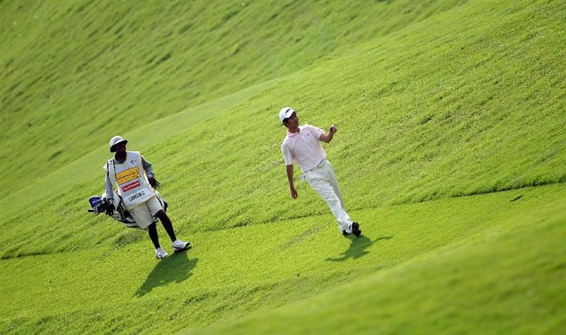 KUALA LUMPUR, MALAYSIA - MARCH 04:  Liang Wen-Chong of China walks with his caddie on the 14th hole during the first round of the Maybank Malaysian Open at the Kuala Lumpur Golf and Country Club on March 4, 2010 in Kuala Lumpur, Malaysia.  (Photo by Andrew Redington/Getty Images)