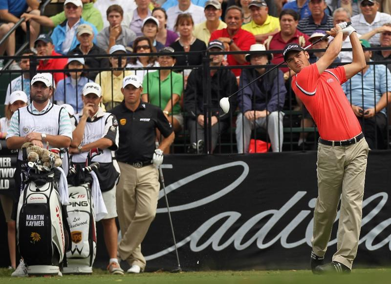 DORAL, FL - MARCH 10:  Martin Kaymer of Germany (R) hits his tee shot on the first hole as Lee Westwood of England  looks on during the first round of the 2011 WGC- Cadillac Championship at the TPC Blue Monster at the Doral Golf Resort and Spa on March 10, 2011 in Doral, Florida.  (Photo by Mike Ehrmann/Getty Images)