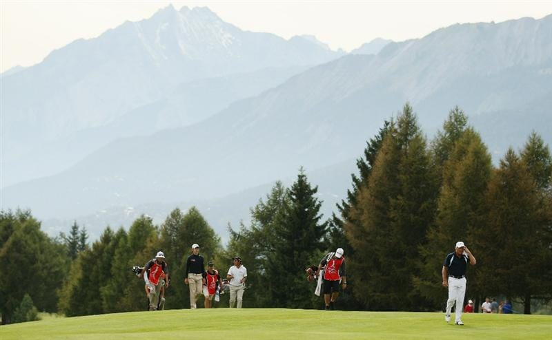 CRANS, SWITZERLAND - SEPTEMBER 02:  Greg Norman of Australia leads his playing partners up the 15th fairway during the first round of The Omega European Masters at Crans-Sur-Sierre Golf Club on September 2, 2010 in Crans Montana, Switzerland.  (Photo by Warren Little/Getty Images)