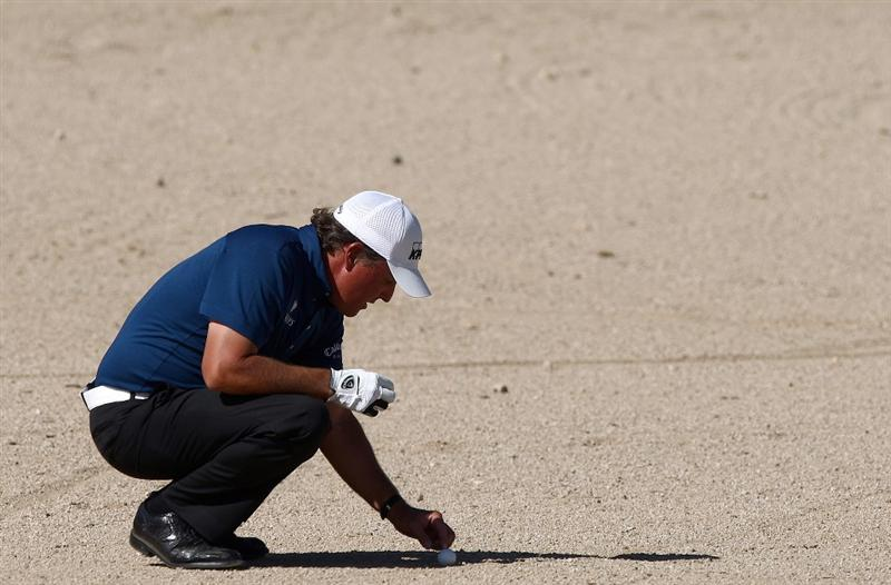 MARANA, AZ - FEBRUARY 27:  Phil Mickelson cleans around his ball after hitting it into the rough on the 17th hole during the third round of the Accenture Match Play Championships at the Ritz-Carlton Golf Club at Dove Mountain on February 27, 2009 in Marana, Arizona. Mickelson lost to Stewart Cink 1-Up. (Photo by Donald Miralle/Getty Images)