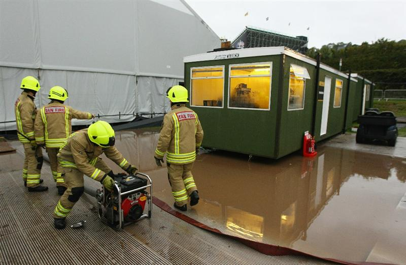 NEWPORT, WALES - OCTOBER 03:  Firefighters pump water from a cabin during the weather delay prior to the restart of the Fourball & Foursome Matches during the 2010 Ryder Cup at the Celtic Manor Resort on October 3, 2010 in Newport, Wales.  (Photo by Richard Heathcote/Getty Images)