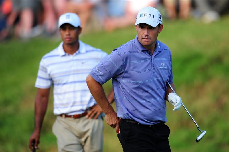 CHASKA, MN - AUGUST 14:  Padraig Harrington of Ireland (R) walks across the 18th green as Tiger Woods looks on during the second round of the 91st PGA Championship at Hazeltine National Golf Club on August 14, 2009 in Chaska, Minnesota.  (Photo by Stuart Franklin/Getty Images)