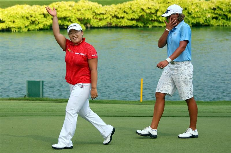 SINGAPORE - MARCH 08:  Jiyai Shin of South Korea (left) waves to the crowd as Katherine Hull of Australia looks dejected after Shin won the HSBC Women's Champions at Tanah Merah Country Club on March 8, 2009 in Singapore.  (Photo by Andrew Redington/Getty Images)