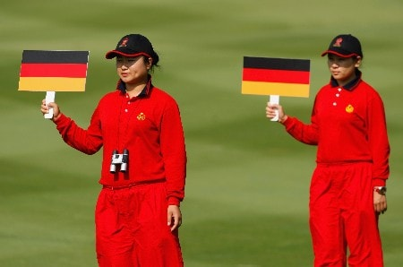 SHENZHEN, CHINA - NOVEMBER 24:  Chinese girls hold flag boards to mark the positions of the ball for the German team during the third round of the Omega Mission Hills World Cup at the Mission Hills Golf Resort on November 24, 2007 in Shenzhen, China.  (Photo by Stuart Franklin/Getty Images)