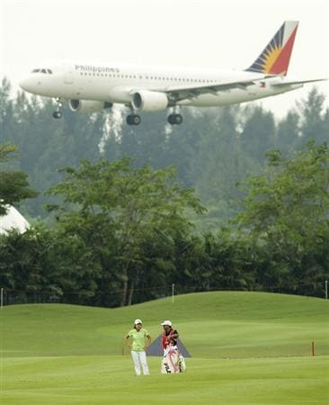 SINGAPORE - MARCH 07:  Eun-Hee Ji of South Korea waits with her caddie on the par five 15th hole as a plane flys overhead during the third round of HSBC Women's Champions at the Tanah Merah Country Club on March 7, 2009 in Singapore.  (Photo by Victor Fraile/Getty Images)